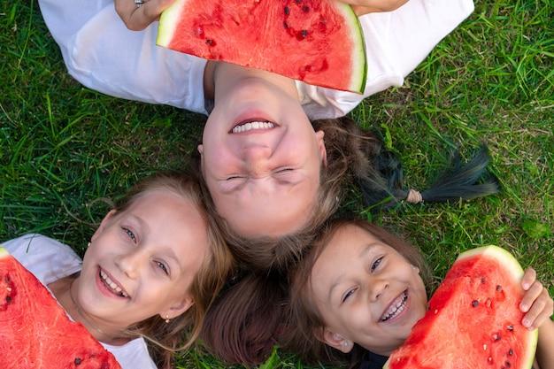 Sommerporträt mit drei schwestern. lächelnde kinder im freien. kinder mit wassermelone. drei glückliches lächelndes kind, das wassermelone im park isst. konzept des sommers.