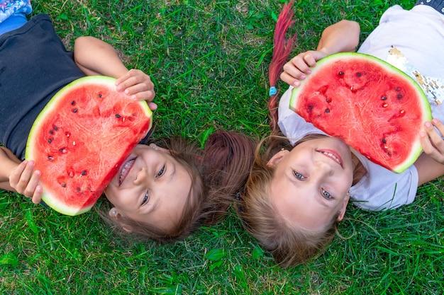 Sommerporträt mit zwei schwestern. lächelnde kinder im freien. kinder mit wassermelone. zwei glückliches lächelndes kind, das wassermelone im park isst. konzept des sommers.