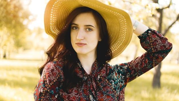 Sommerporträt, schöne junge frau, die strohhut zur sonnenuntergangszeit auf dem garten trägt