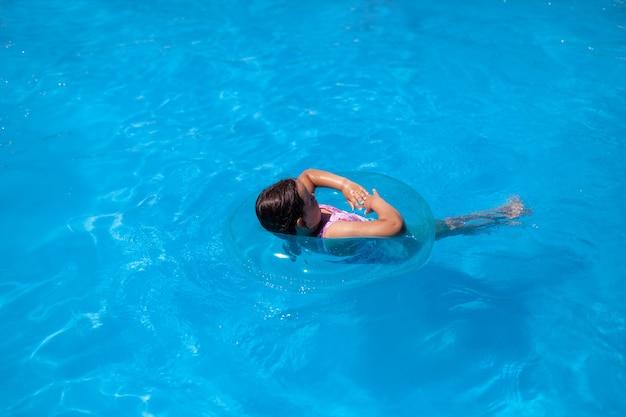 Sommerpostkarte mit blick auf das meer und ein kind, das in einem blauen aufblasbaren kreis auf dem meer schwimmt...