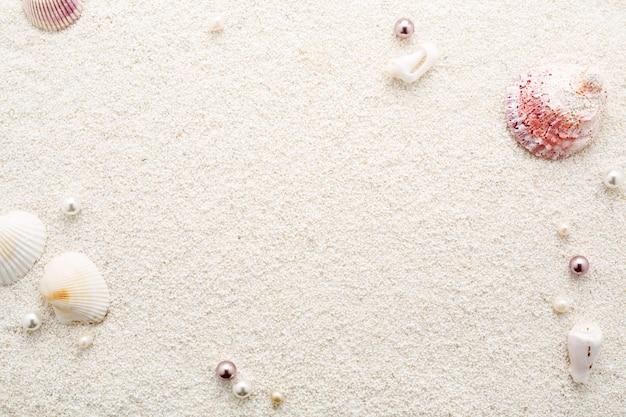 Sommerrahmen von muscheln und perlen auf weißem strandsand