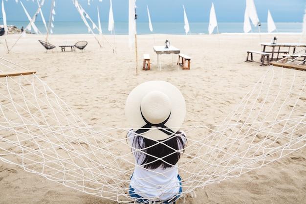 Sommerreiseferienkonzept, glückliche asiatische frau des alleinreisenden mit weißem ärmellosem hemd und hut entspannen in der hängematte am tropischen strand in hua hin, thailand