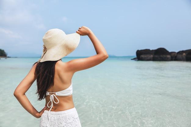 Sommerreiseferienkonzept, glückliche reisende asiatische frau mit bikini und strohhut, die auf seestrand bei koh mak, trad, thailand gehen