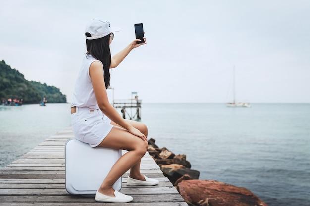 Sommerreiseferienkonzept, glückliche reisende asiatische frau mit handy und koffer entspannen auf holzbrücke im meeresstrand bei koh kood, trad, thailand