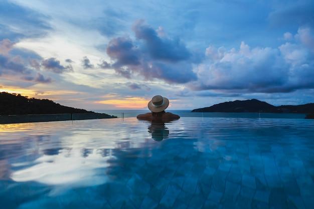 Sommerreiseferienkonzept, glückliche reisende asiatische frau mit hut und bikini entspannen im luxuriösen infinity-poolhotel