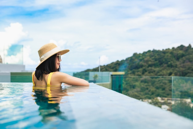 Sommerreiseferienkonzept, glückliche reisende asiatische frau mit hut und bikini entspannen im luxus-infinity-pool-hotelresort mit meeresstrandhintergrund am tag in phuket, thailand