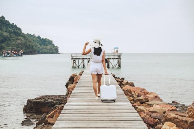Sommerreiseferienkonzept, glückliche reisende asiatische frau mit koffertasche und strohhut, die auf hölzerne brücke im seestrand bei koh kood, trad, thailand gehen