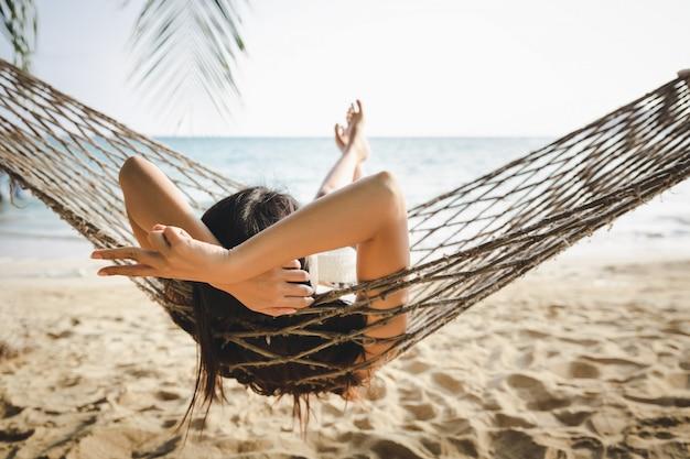 Sommerreiseferienkonzept, glückliche reisende asiatische frau mit weißem bikini entspannen in der hängematte am strand in koh mak, thailand