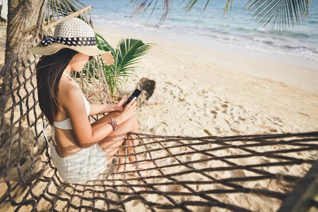 Sommerreiseferienkonzept, glückliche reisende asiatische frau mit weißem bikini unter verwendung des mobiltelefons und entspannen in der hängematte am strand in koh mak, thailand