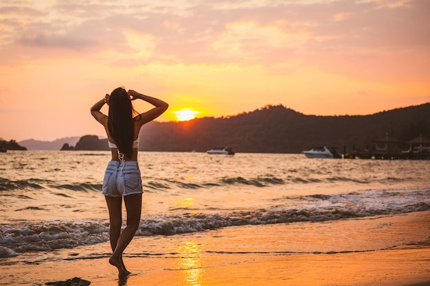 Sommerreiseferienkonzept, reisende asiatische frau mit bikini entspannen am strand bei sonnenuntergang in koh mak, thailand