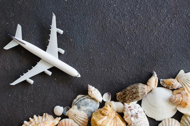 Sommerreisekonzept. dekoratives flugzeug und verschiedene muscheln auf dunklem betonhintergrund.