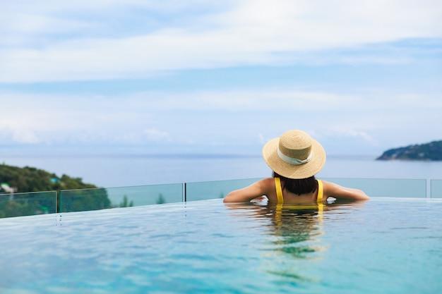 Sommerreiseurlaubskonzept, glückliche reisende asiatische frau mit hut und bikini entspannen im luxus infinity pool hotel resort