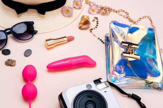 Sommerreisezubehör. damen set von spielzeug für erwachsene, kamera, hut, brille auf rosa