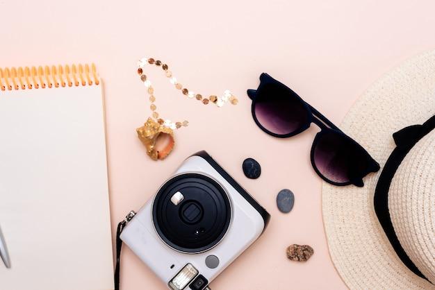 Sommerreisezubehör. kamera, hut, brille und ein flacher notizblock, draufsicht