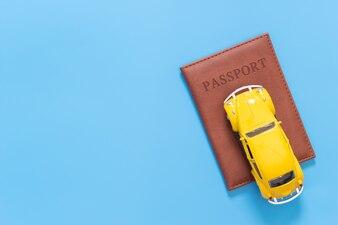 Sommerreisezubehör mit Pass und Auto auf Blau
