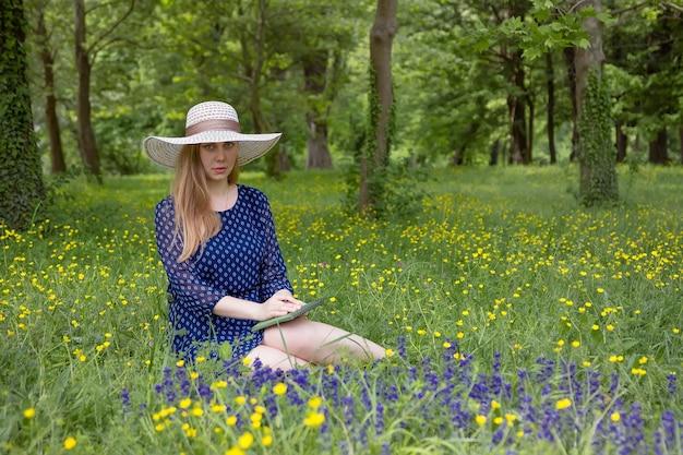 Sommersaison. attraktive frau in einem hut und einem blauen kleid mit einem notizbuch