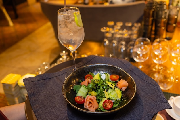 Sommersalat auf einem weißen teller mit einem kellner in der hand.