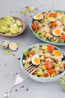 Sommersalat mit eiern und gemüse in schalen