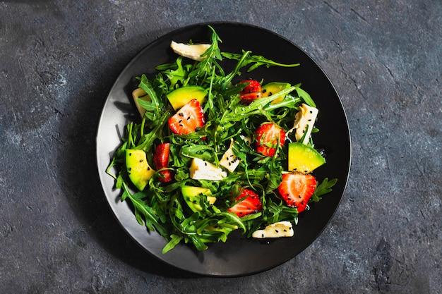 Sommersalatschüssel mit rucola, erdbeere, briekäse, kümmel und honig auf schwarzer wand. konzept für gesunde ernährung. flatlay mit copyspace. nahansicht. hartes licht