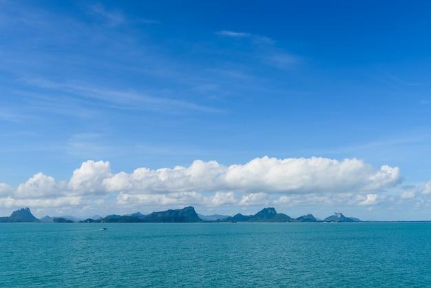 Sommerseelandschaft mit grünem insel- und blauem himmelhintergrund