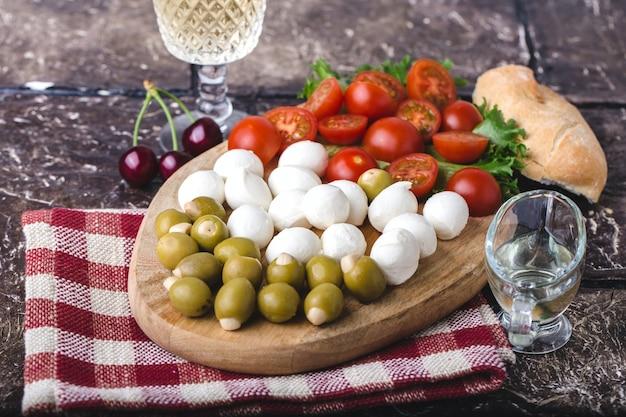 Sommersnack aus mozzarella, tomaten, oliven und grüns auf holzbrett, mit glas weißwein, stück baguette, olivenöl und rot karierter serviette. brauner hintergrund