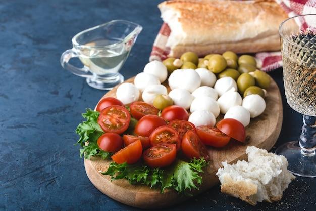 Sommersnack aus mozzarella, tomaten, oliven und grüns auf holzbrett, mit glas weißwein, stück baguette, olivenöl und rot karierter serviette. dunkelblauer hintergrund