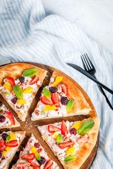 Sommersnacks. essen für die party. fruchtpizza mit sahne, johannisbeeren, joghurt, erdbeeren, mango, pfirsichen, bananen, brombeeren, schokolade, walnüssen, minze. auf hellblauem tisch. copyspace