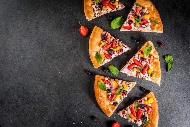 Sommersnacks. essen für die party. fruchtpizza mit sahne, johannisbeeren, joghurt, erdbeeren, mango, pfirsichen, bananen, brombeeren, schokolade, walnüssen, minze. auf schwarzem tisch. copyspace draufsicht