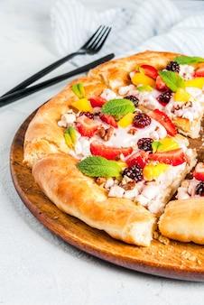 Sommersnacks. essen für die party. fruchtpizza mit sahne, korinthen, joghurt und früchten
