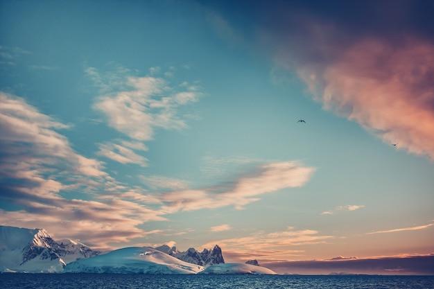 Sommersonnenuntergang in der antarktis. farbige sonnenuntergangswolken über dem ozean mit bergen im hintergrund. schöne winterlandschaft