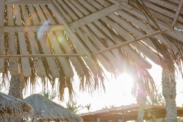 Sommersonnenuntergangregenschirme auf dem sandigen strand.