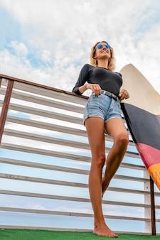 Sommerspaß im urlaub reisen urlaub. surfen. sexy schönes surfermädchen mit surfbrett. gesunder lebensstil. extremer wassersport. sommer freizeitbeschäftigung. hobby. wellness-konzept