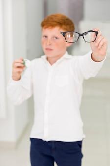 Sommersprossenjunge, der brillen und kontaktlinsenbehälter hält