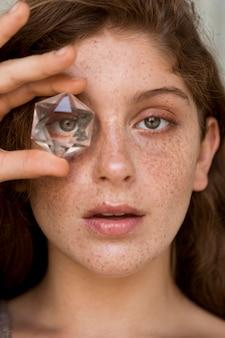Sommersprossige frau, die ein auge mit kristall bedeckt