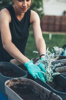 Sommersprossige kaukasische frau, die blumen zu hause im hinterhof mit handschuhen und lächeln umtopft