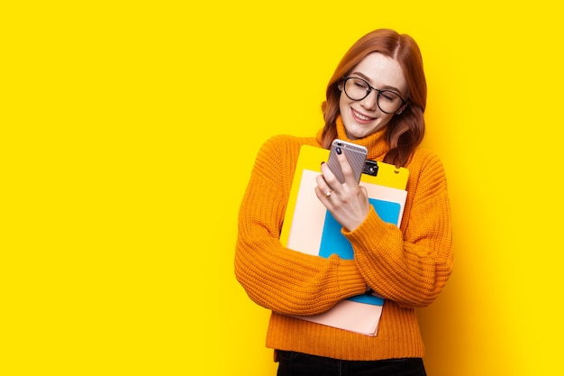 Sommersprossiger ingwer-student mit telefon auf gelbem hintergrund sms-chat-bildungskonzept