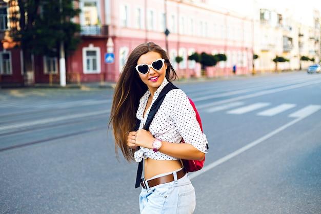 Sommerstadtporträt des stilvollen jugendlich girt, allein mit rucksack reisend, schönen tag in der neustadt habend, genießen sie ihren urlaub, tragen sie rucksack, hipsterbrille und lässigen blick, freude, gefühle
