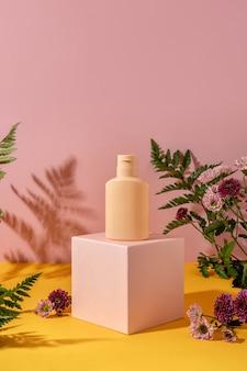 Sommerstil der vitrine für die produktpräsentation von kosmetikprodukten auf gelbem und rosa hintergrund. kosmetikprodukt in flaschen auf einem rosafarbenen podium abfüllen.