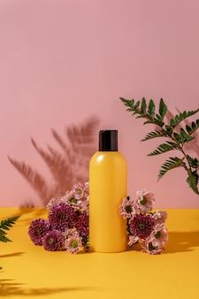 Sommerstil der vitrine für kosmetikproduktpräsentation auf gelbem und rosa hintergrund mit blumen. gelbes flaschenkosmetikprodukt mit blumen