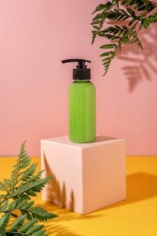 Sommerstil der vitrine für kosmetikproduktpräsentation auf gelbem und rosa hintergrund mit blumen. kosmetikprodukt der grünen flasche auf einem rosafarbenen podium
