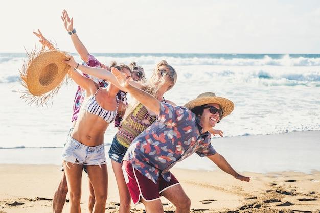 Sommerstilgruppe junger fröhlicher leute, die zusammen spaß haben und viel lachen im urlaubsurlaub am strand - meereswellen und blauer himmel im hintergrund - lebensstil der touristen