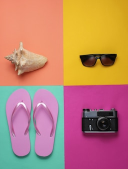 Sommerstillleben. strandzubehör. modische rosa flipflops, retro-kamera, muschel, sonnenbrille auf farbigem papierhintergrund.