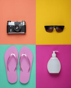 Sommerstillleben. strandzubehör. modische rosa flipflops, retro-kamera, sonnenschutzflasche, sonnenbrille auf farbigem papierhintergrund.