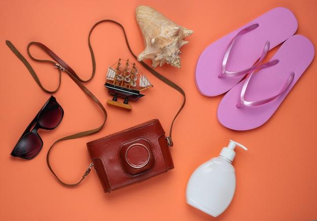 Sommerstillleben. strandzubehör. modische rosa flipflops, retro-kamera, sonnenschutzflasche, sonnenbrille, muschel auf korallenpapierhintergrund.