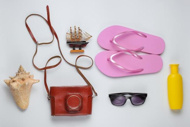 Sommerstillleben. strandzubehör. modische rosa flipflops, retro-kamera, sonnenschutzflasche, sonnenbrille, muschel auf weißem papierhintergrund.