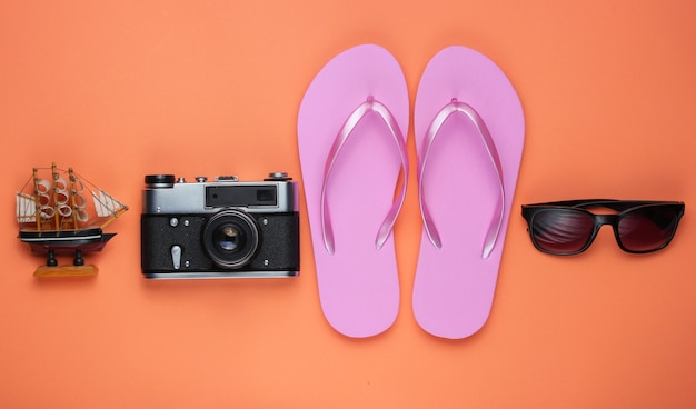 Sommerstillleben. strandzubehör. modische rosa flipflops, tasche, retro-kamera, sonnenbrille, schiff auf korallenpapierhintergrund.