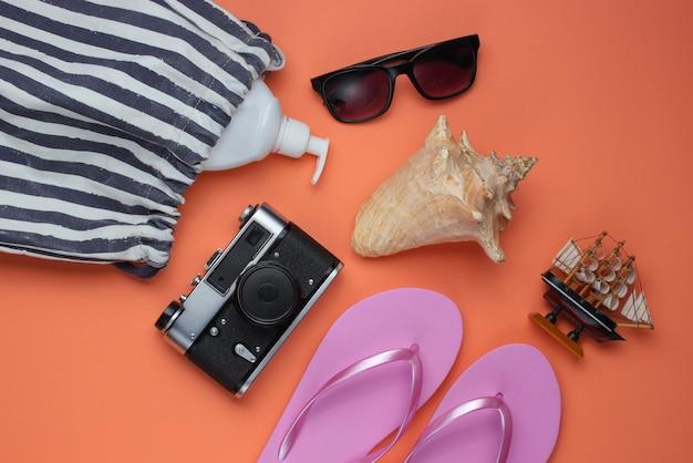 Sommerstillleben. strandzubehör. modische rosa flipflops, tasche, retro-kamera, sonnenschutzflasche, sonnenbrille, muschel auf korallenpapierhintergrund.