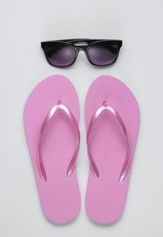 Sommerstillleben. strandzubehör. modische strandrosa flipflops, sonnenbrille auf weißem papierhintergrund.
