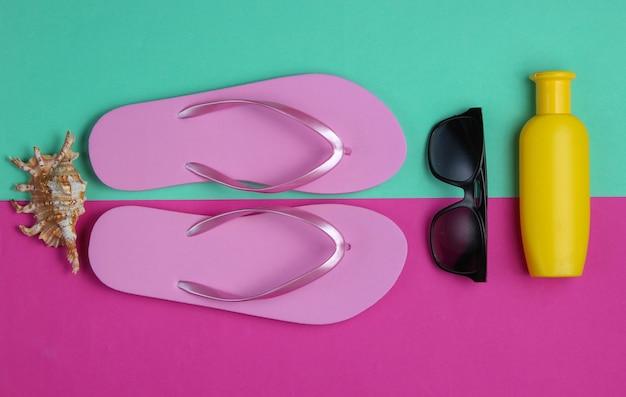 Sommerstillleben. strandzubehör. modische strandrosa-flipflops, sonnenschutzflasche, sonnenbrille, muschel auf rosa blauem papierhintergrund.