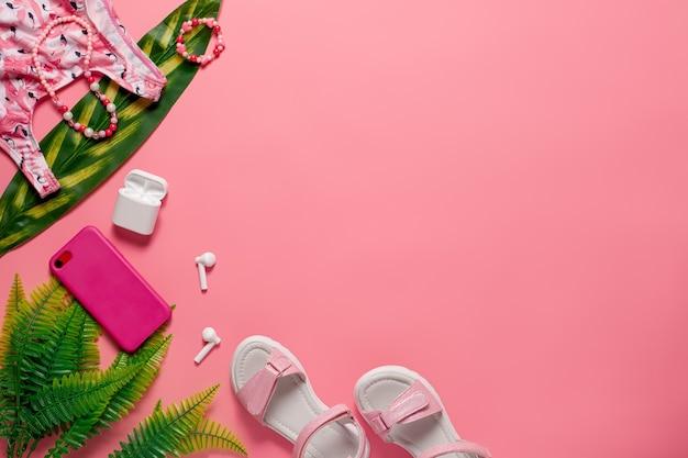 Sommerstrand draufsicht konzept kinder sommerkleidung und accessoires auf dem rosa hintergrund mit g...